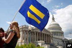 "Seorang pendukung LGBT mengibarkan ""bendera kesetaraan"" dalam unjuk rasa menentang rencana pemerintah AS melarang kaum LGBT berkarier di militer, di Capitol Hill, Washington, 26 Juli 2017."