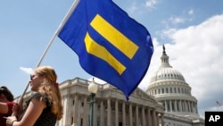"A supporter of LGBT rights holds up an ""equality flag"" on Capitol Hill in Washington, July 26, 2017, during an event held by Rep. Joe Kennedy, D-Mass., in support of transgender members of the military, in response to President Donald Trump's declaration that he wants transgender people barred from serving in the U.S. military ""in any capacity,"" citing ""tremendous medical costs and disruption."""