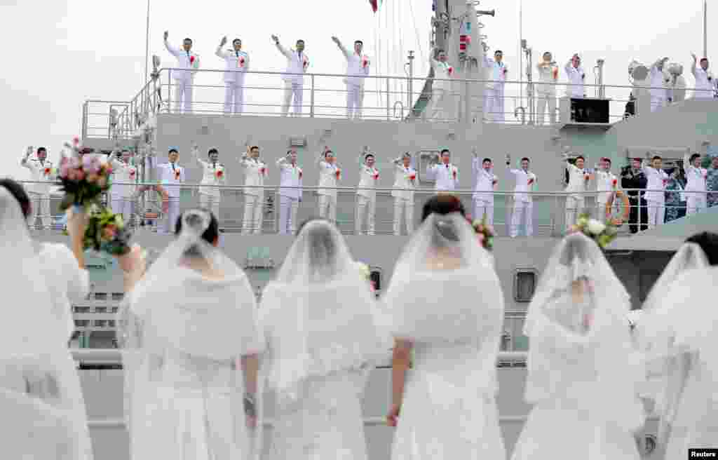Navy personnel of the People's Liberation Army (PLA) wave at their brides during a mass wedding at a military base in Zhoushan, Zhejiang province, China.