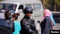 Police from Special Weapons and Tactics (SWAT) team stand guard outside the South Railway Station, where three people were killed and 79 wounded in a bomb and knife attack on Wednesday, in Urumqi, Xinjiang, Uighur Autonomous region, May 1, 2014.