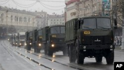 FILE - Police vehicles drive through a street during an opposition rally in Minsk, Belarus, March 25, 2017. A cordon of club-wielding police blocked the demonstrators' movement along Minsk's main avenue near the Academy of Science. Hulking police detention truck