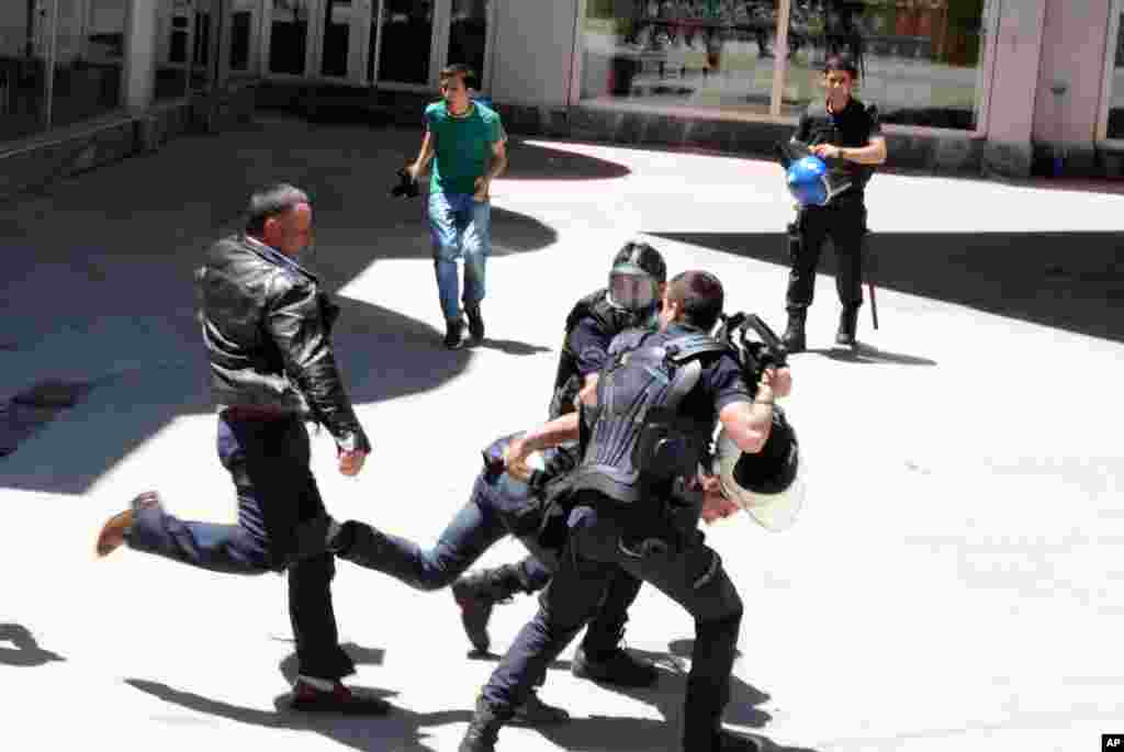 Polisi anti huru-hara Turki mencoba melindungi seseorang dari kelompok tak dikenal yang menyerang reli pro Partai Demokrat Rakyat Kurdi (HDP) di timur kota Erzurum.