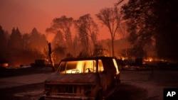 지난 8일 미국 캘리포니아주 파라다이스 마을에 화재가 발생한 가운데 공터에 세원진 차 한대가 불에 타고 있다.