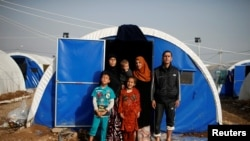 Displaced Iraqi Gorha Mahmoud (left), 40, poses for a photograph with family at Hammam al-Alil camp south of Mosul, Iraq, March 29, 2017.