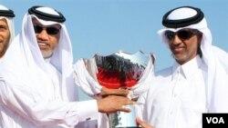 Presiden AFC Mohamed Bin Hammam, kiri, and Ketua Federasi Sepakbola Qatar Sheikh Hamad Bin Khalifa Bin Ahmed al-Thani, memegang trofi Piala Asia yang tiba di bandara internasional Doha hari Senin (3/1).