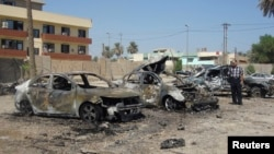 Seorang pria memeriksa rongsokan mobil setelah ledakan bom mobil di distrik Kadhimiya, Baghdad hari Senin (30/9).