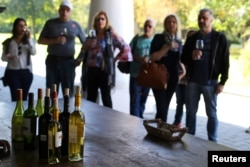 People attend a wine tasting event at a vineyard near Santiago, Chile, April 6, 2017.