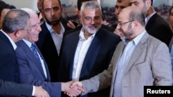 Senior Fatah official Azzam Al-Ahmed (L) shakes hands with senior Hamas leader Moussa Abu Marzouq after announcing a reconciliation agreement in Gaza City, April 23, 2014.
