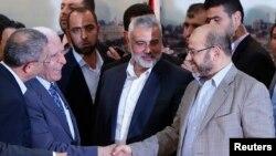 Giới chức cấp cao của nhóm Fatah Azzam Al-Ahmed (trái) bắt tay với thủ lĩnh nhóm Hamas Moussa Abu Marzouq sau khi công bố thỏa thuận tại thành phố Gaza, ngày 23/4/2014.