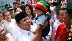 Calon presiden Indonesia Prabowo Subianto menggendong bayi dalam kampanye di Bandung (5/6). (AP/Kusumadireza)