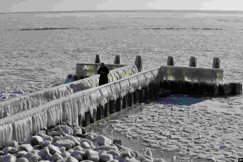 A woman takes pictures of icicles on a jetty at the Afsluitdijk, a dike separating IJsselmeer inland sea, and the Wadden Sea, Netherlands.