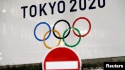 东京街头交通警示牌后的东京奥运会的标识。(2020年3月23日)