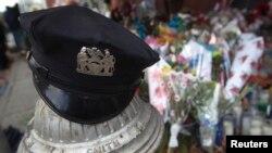 Sebuah topi polisi diletakkan di lokasi penembakan dua polisi saat bertugas di wilayah Brooklyn, New York (25/12).