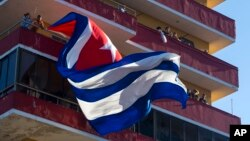FILE - People watch a concert given by Puerto Rico's Olga Tanon, from a building flying a Cuban flag in Havana, Cuba, Saturday, Dec. 12, 2015.