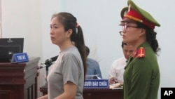 Prominent blogger Nguyen Ngoc Nhu Quynh, left, stands trial in the south central province of Khanh Hoa, Vietnam, June 29, 2017. She was accused of distorting government policies and defaming the Communist regime on her Facebook posts, her lawyer said.