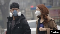 "FILE - A couple wear masks to protect their lungs from air pollution on Dec. 8, 2015, the first time Chinese authorities declared a ""red alert"" for air quality in Beijing. The country's environmental minister has warned local governments to enforce regulations or face consequences."