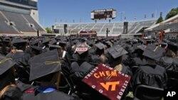 Los estudiantes siguen el discurso de la primera dama, Michelle Obama durante la ceremonia de graduación en Virginia Tech.