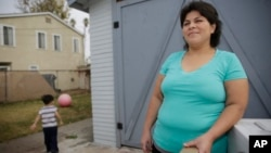 FILE - Central American refugee Roxana Janet Castillo poses for a photo at her home in Los Angeles, Dec. 10, 2015. Castillo applied for the Central American Minors (CAM) Refugee/Parole Program to bring her three children legally from her native El Salvador as refugees or with a humanitarian parole. Her son is at left.