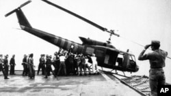 U.S. Navy personnel aboard the USS Blue Ridge push a helicopter into the sea off the coast of Vietnam in order to make room for more evacuation flights from Saigon on April 29, 1975.