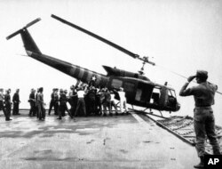 FILE - U.S. Navy personnel aboard the USS Blue Ridge push a helicopter into the sea off the coast of Vietnam in order to make room for more evacuation flights from Saigon, April 29, 1975.