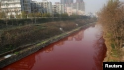 A view of red polluted water in the Jianhe River in Luoyang, Henan province, China, December 13, 2011.