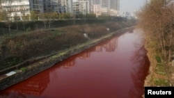 A view of red polluted water in the Jianhe River in Luoyang, Henan province, December 13, 2011. According to local media, the sources of the pollution are two illegal chemical plants discharging their production waste water into the rain sewer pipes.