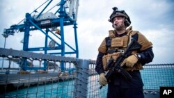 A security forces member stands guard aboard the Norwegian frigate Helge Ingstad, in Limassol, Cyprus, Dec. 28, 2013.