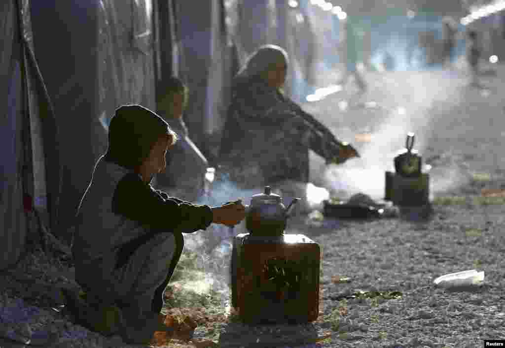 Kurdish refugees from the Syrian town of Kobani prepare tea in a camp in the southeastern town of Suruc, Sanliurfa province.