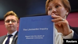 Marina Litvinenko widow of Alexander Litvinenko poses with a copy of The Litvinenko Inquiry Report with her son Anatoly (L) during a news conference in London, Britain, Jan. 21, 2016.