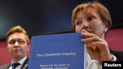 "Marina Litvinenko, widow of ex-KGB agent Alexander Litvinenko, poses with a copy of ""The Litvinenko Inquiry"" with her son, Anatoly, during a news conference in London, Jan. 21, 2016."