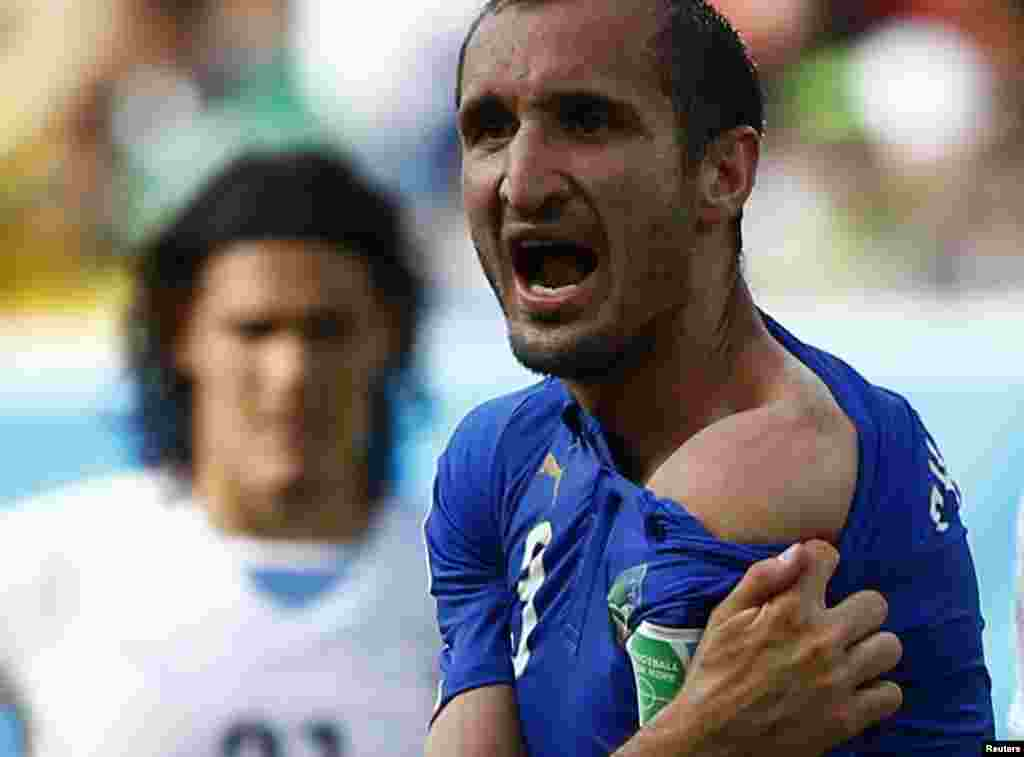 Italy's Giorgio Chiellini shows his shoulder, claiming he was bitten by Uruguay's Luis Suarez, during their 2014 World Cup Group D soccer match at Dunas arena in Natal, Brazil, June 24, 2014.