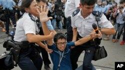 Seorang pengunjuk rasa prodemokrasi diamankan polisi dari lokasi unjuk rasa di Hong Kong (3/10/2014).