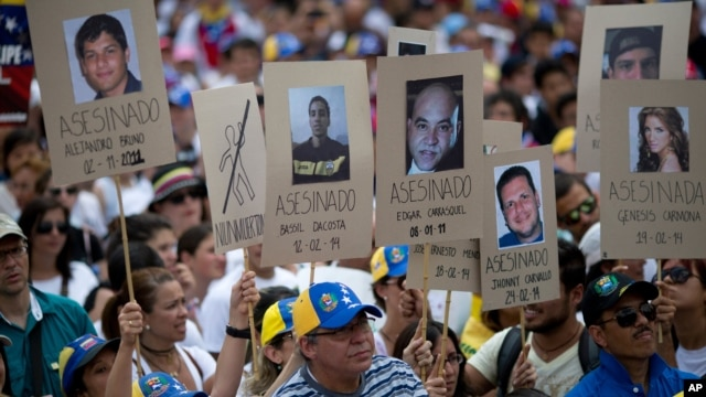 FILE - Demonstrators hold up posters with images of Venezuelans who were killed in the past two weeks during the recent unrest, at a rally with human rights activists in Caracas, Venezuela, Feb. 28, 2014.