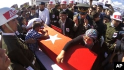 Fehime Aydemir (R), the mother of Turkish officer Metin Aydemir, cries over his coffin during funeral services in his hometown of Erzurum, Turkey, Aug. 19, 2015. Aydemir was one of the three officers killed Tuesday in an operation against Kurdish PKK rebels.