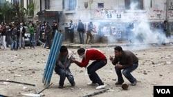 Para pengunjuk rasa berlindung di balik potongan pagar saat polisi melemparkan gas air mata di lapangan Tahrir, Cairo, Mesir (20/11).