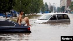 一名男子坐在暴雨後鄭州街頭漂浮的汽車上。 (2021年7月22日)