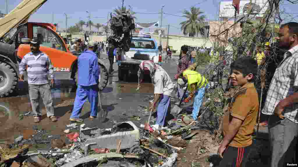 Street cleaners remove debris after a car bomb exploded in Diwaniya province, south of Baghdad, April 29, 2013.
