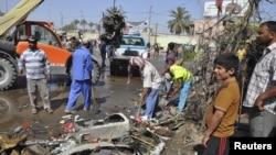 2013年4月29日巴格达以南150公里远的迪瓦尼耶地方发生一次汽车炸弹爆炸事件之后,请道工人正在清除爆炸碎片瓦砾