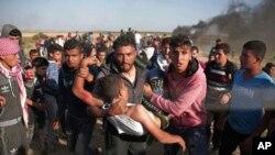 مارچ ٣١، فلسطینیان د غزې او اسرائیل پر پوله باندې د اسرائیلي سرتیرو په ډزو یو ټپي شوی کس روغتون ته وړي.