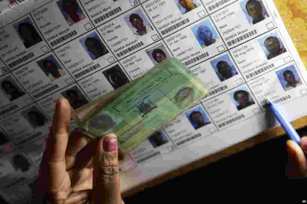 An election official verifies the particulars of a person on the electoral roll during presidential election day in Lusaka, Tuesday, Jan. 20, 2015.