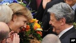 독일의 새 대통령으로 선출된 뒤 앙겔라 메르켈 총리(좌)로부터 축하 꽃다발을 받는 옛 동독 민주화 운동가 출신인 요하임 가우크(우) 당선자