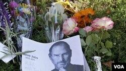 Para kerabat dan sahabat almarhum Steve Jobs mengirimkan karangan bunga di luar rumahnya di Palo Alto, California (7/10).