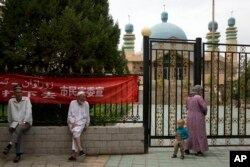 In this photo taken Thursday, July 17, 2014, Uighur residents gather outside a mosque in the city of Aksu in western China's Xinjiang Uighur Autonomous Region..