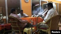 Customers smoke water pipes at a shisha cafe in Khartoum, April 28, 2013