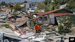 Rescuers carry a body bag containing the remains of an earthquake victim through a neighborhood flattened by Friday's earthquake in Palu, Central Sulawesi, Indonesia, Oct. 2, 2018.
