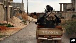 Un homme des forces armées libyennes se prépare à combattre des membres du groupe Etat islamique à l'ouest de Benghazi, Libye, le 7 mars 2016.