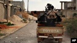 Un élément des forces armées libyennes est assis à l'arrière d'un véhicule qui avance dans l'ouest de Benghazi, en Libye.