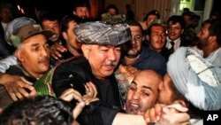 FILE - General Abdul Rashid Dostum, center in gray turban, leader of Afghanistan's Uzbek community returns to Kabul from exile, Aug. 16, 2009.