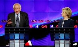 Hillary Rodham Clinton listens as Sen. Bernie Sanders, of Vermont, speaks during the CNN Democratic presidential debate in Las Vegas, Oct. 13, 2015.