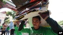 Filipinski radnik nosi postere uklonjene po završenim izborima u gradu Kuezon